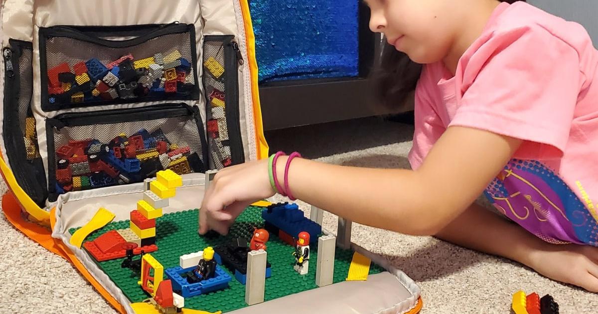 little girl on floor using lego backpack