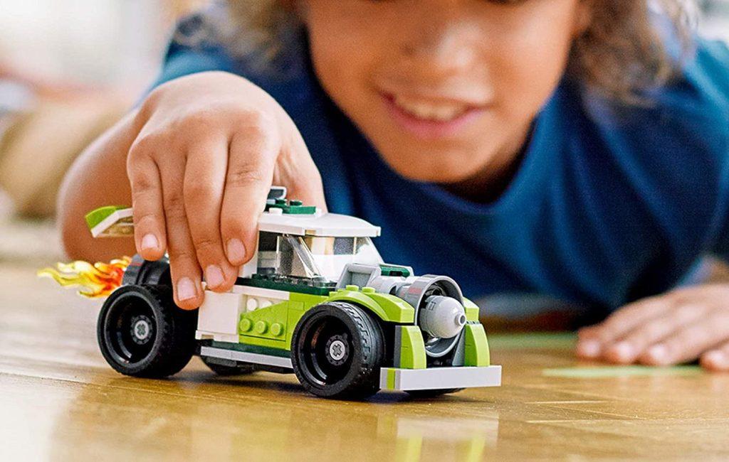 boy playing with lego creator rocket trucj