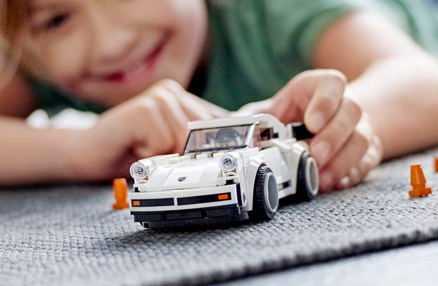boy playing with lego speed white car