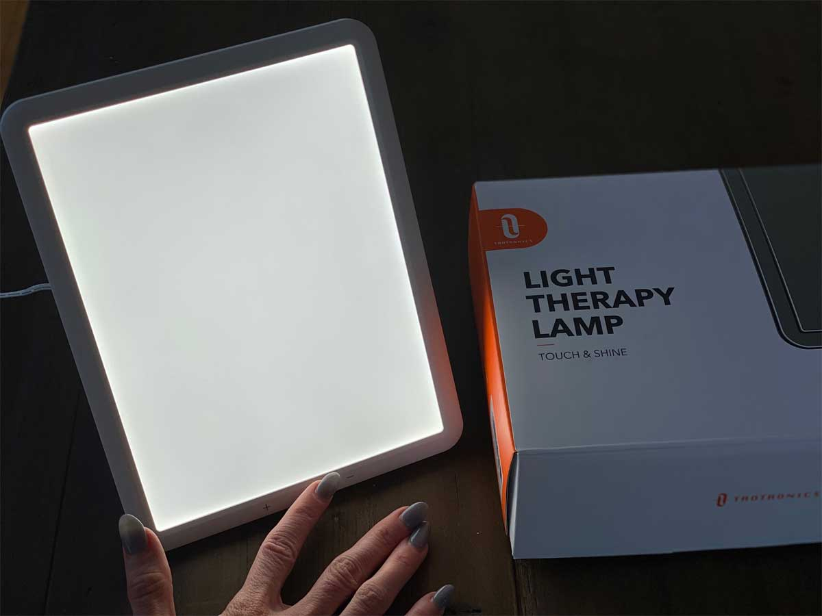 hand showing touch button on illuminated light therapy lamp