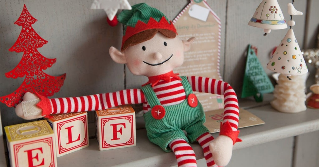 little elf on the shelf next to blocks and toys