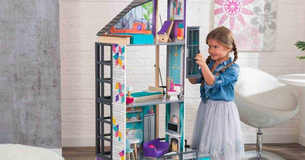 little girl playing with dollhouse