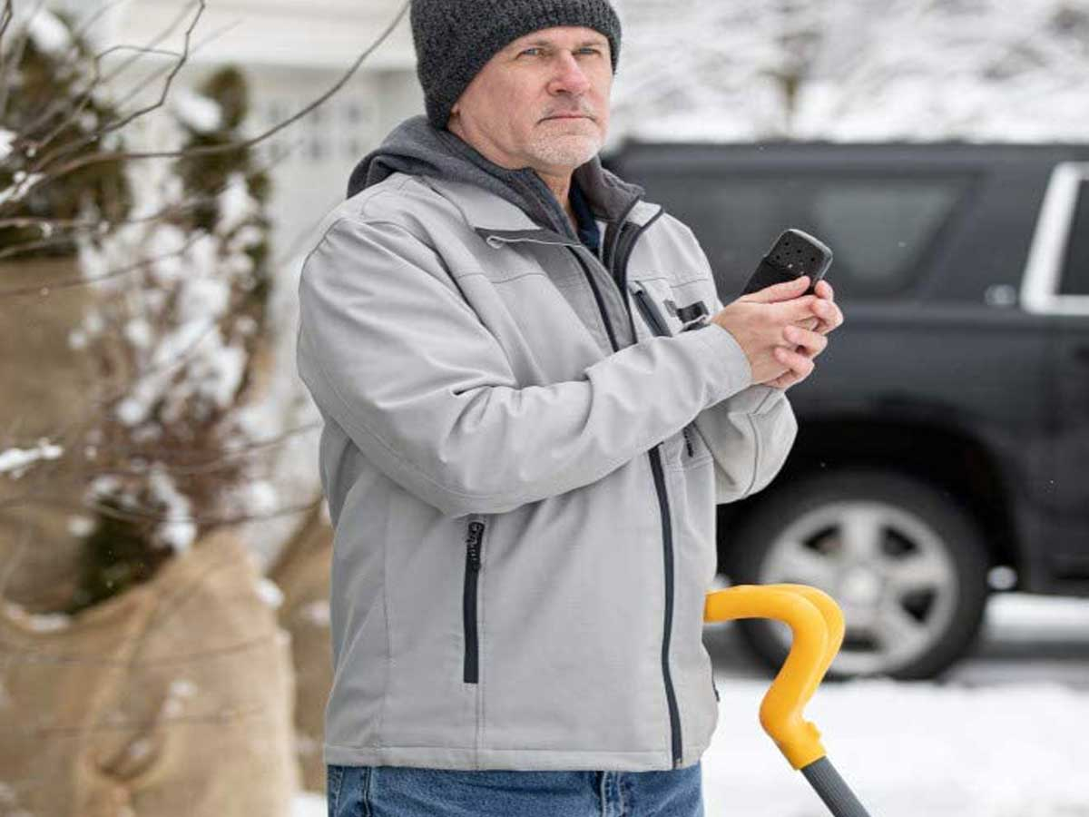 man outside shoveling with hand warmer