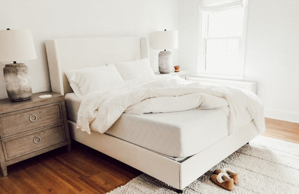white bedding with corner of mattress pulled up