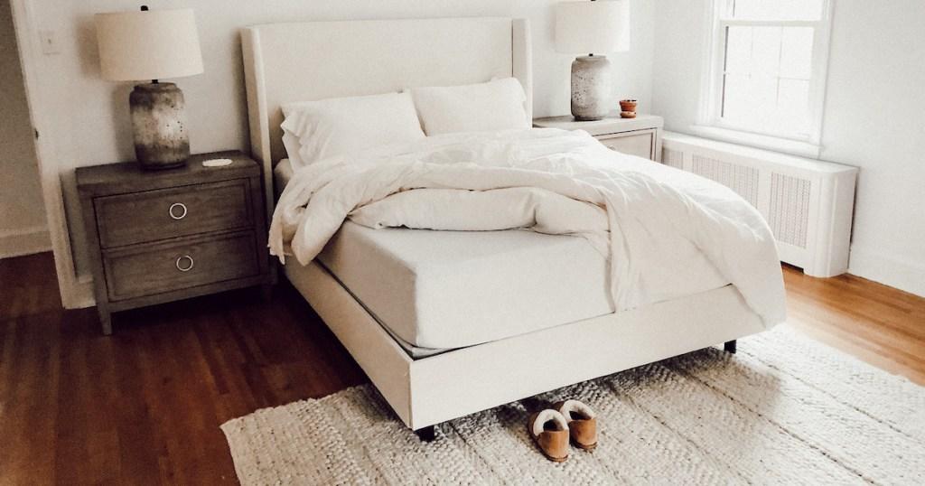 white bedding with sheets taken off corner of zinus mattress