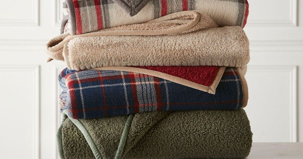 folded pile of sherpa throw blankets