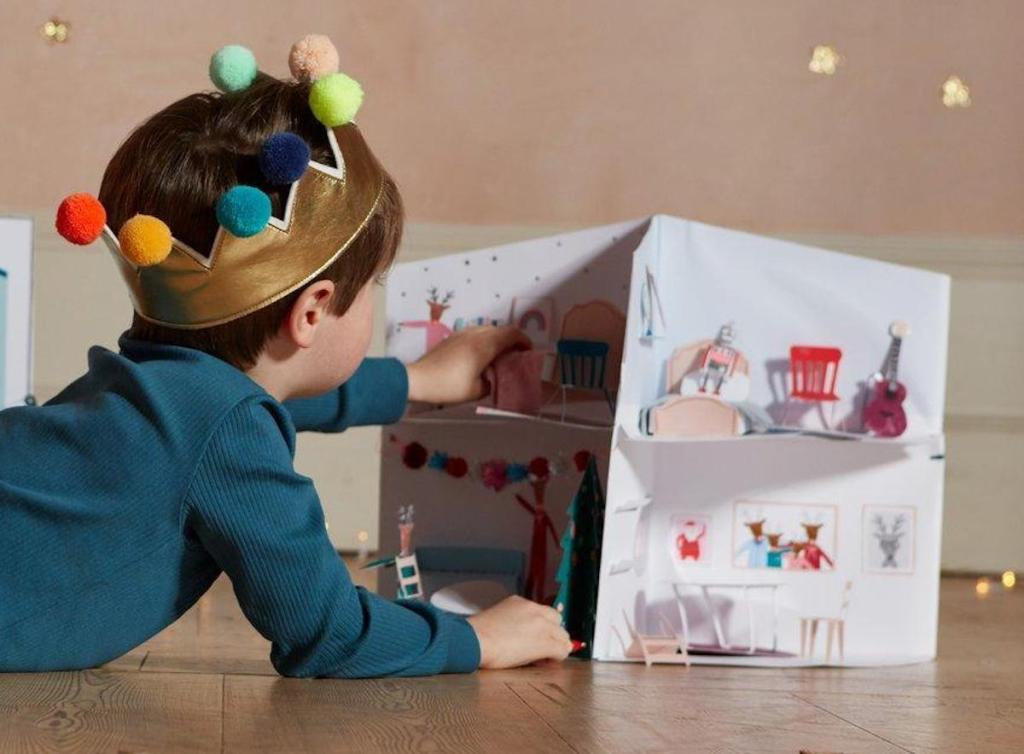 boy wearing gold pom crown playing with paper doll house