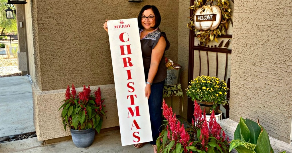 woman holding a merry christmas porch sign