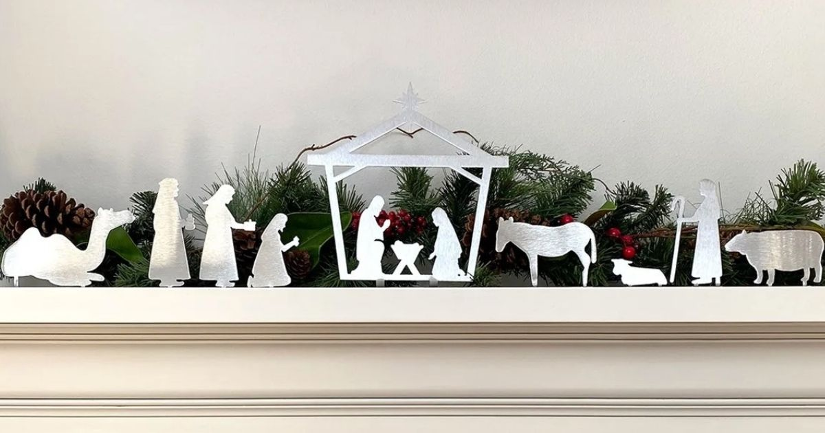 metal nativity set displayed in front of greenery on a hearth