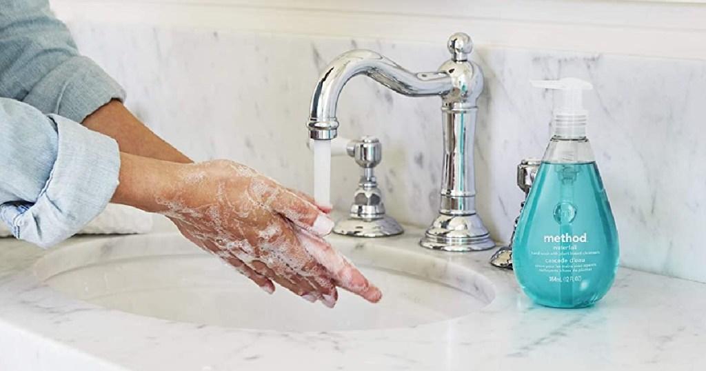 person washing hands in bathroom sink