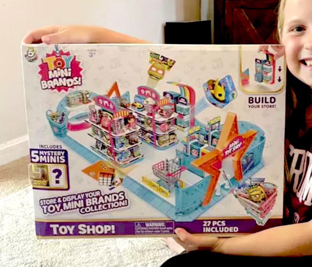 kid holding mini brands toy store box
