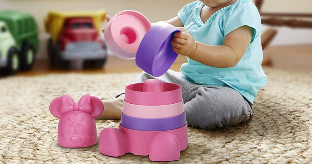 baby playing with pink stackable toy