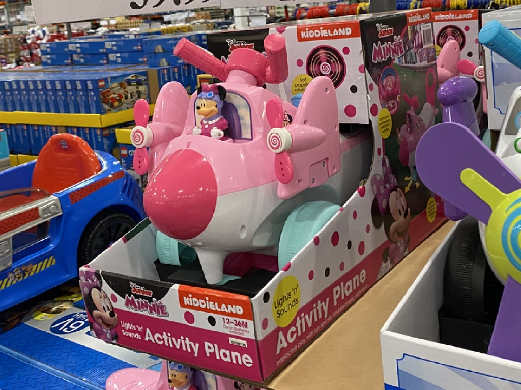 pink little toy plane in store with Minnie Mouse toy on it