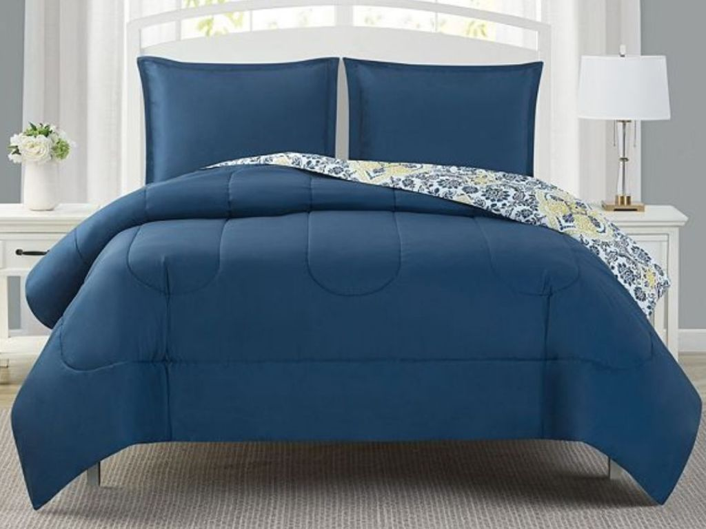 blue and floral reversible bedding on bed in bedroom