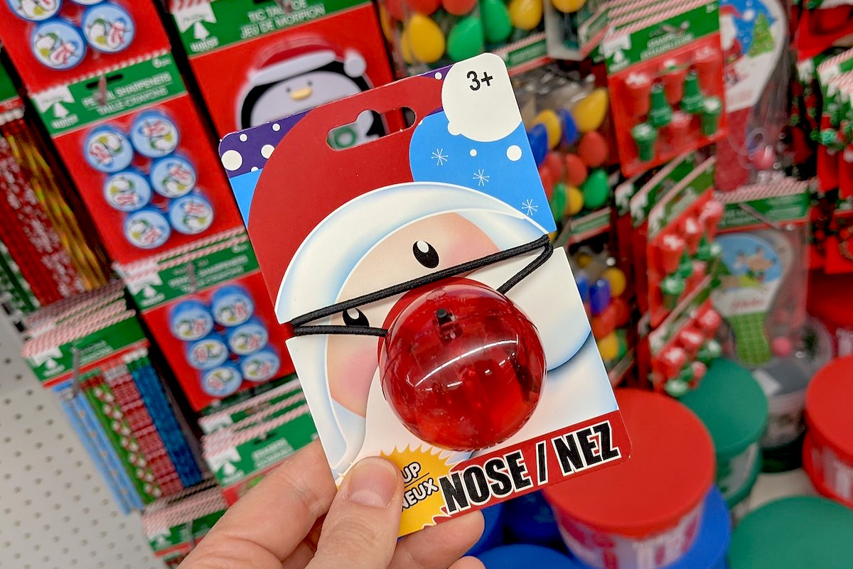 hand holding a red reindeer nose in dollar tree christmas decorations store aisle