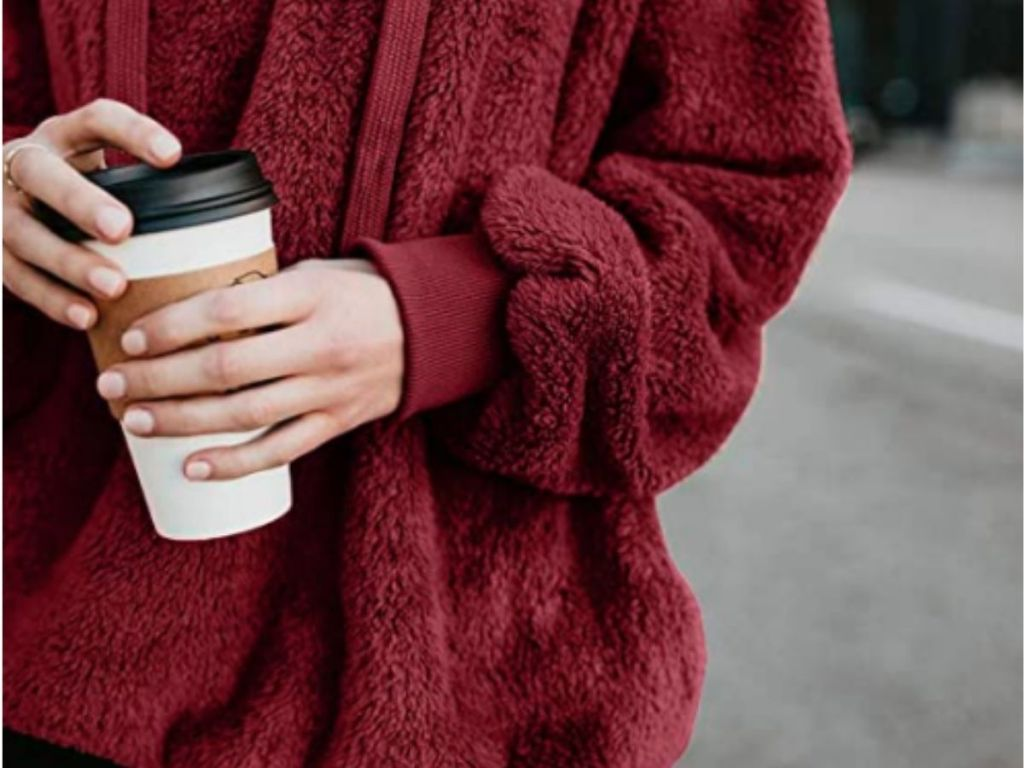close up of red sherpa sweater with woman holding coffee cup