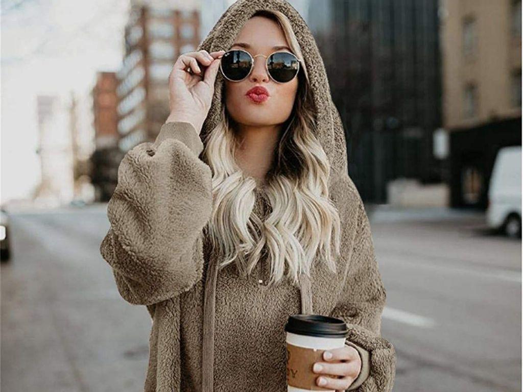 woman wearing tan sherpa sweater holding coffee and wearing sunglasses