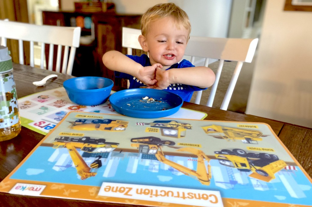 boy sitting at table with blue dishes on table