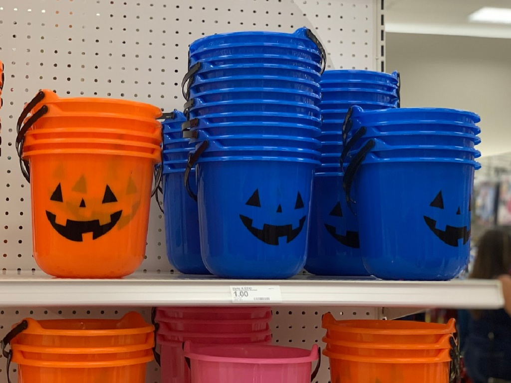 plastic buckets in the shapes of pumpkins on store shelf
