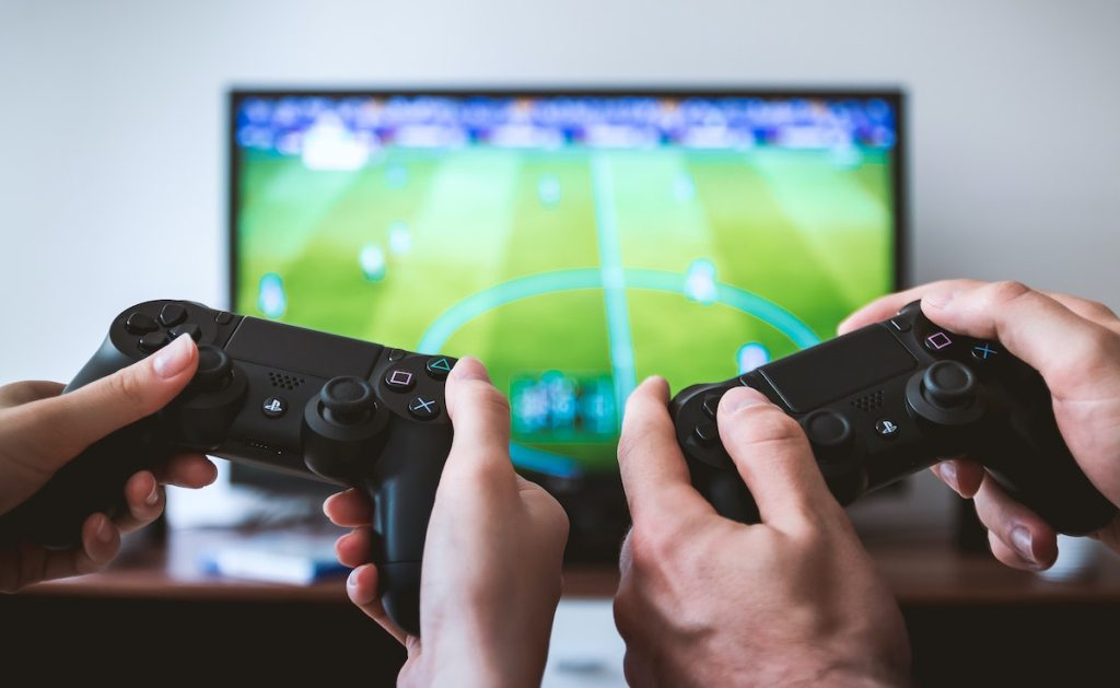 two hands holding gaming remote controls in front of football tv screen