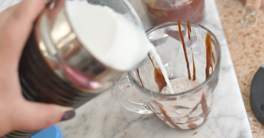 pouring hot frothed milk into coffee cup