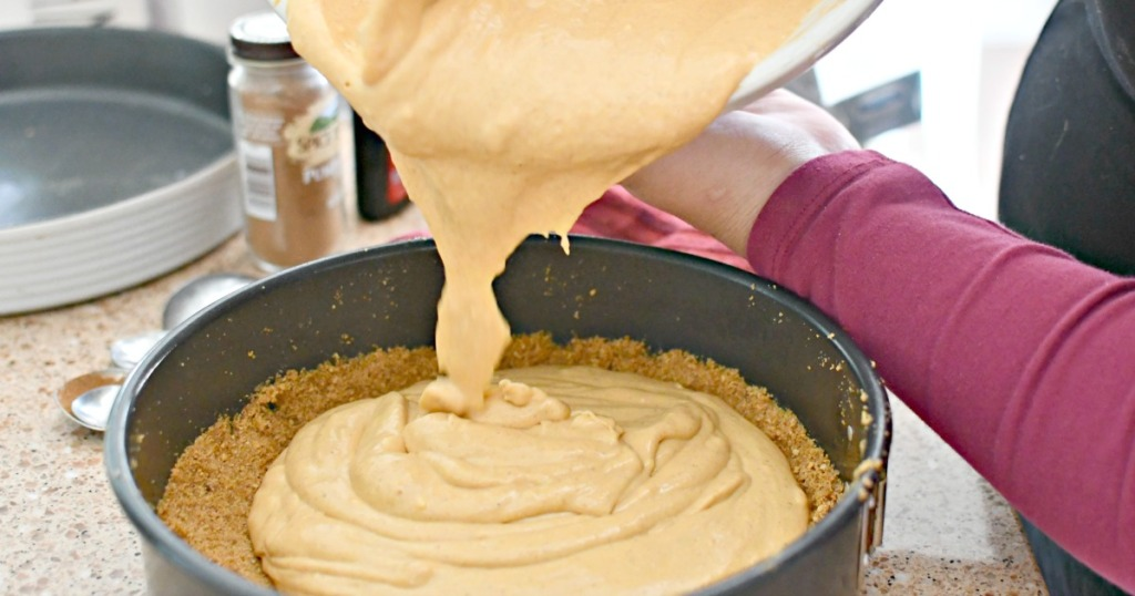 pouring pumpkin cheesecake filling into pan