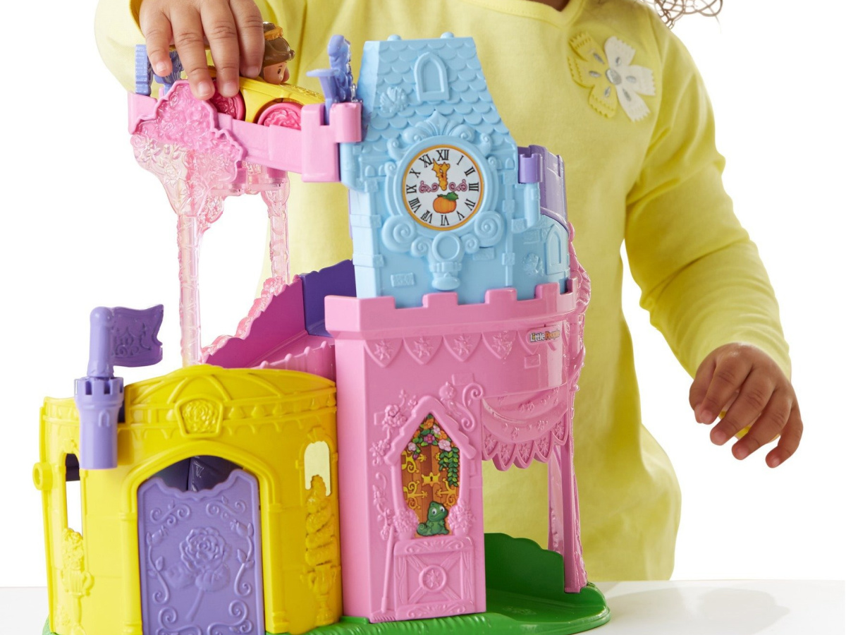little girl playing with pink castle set