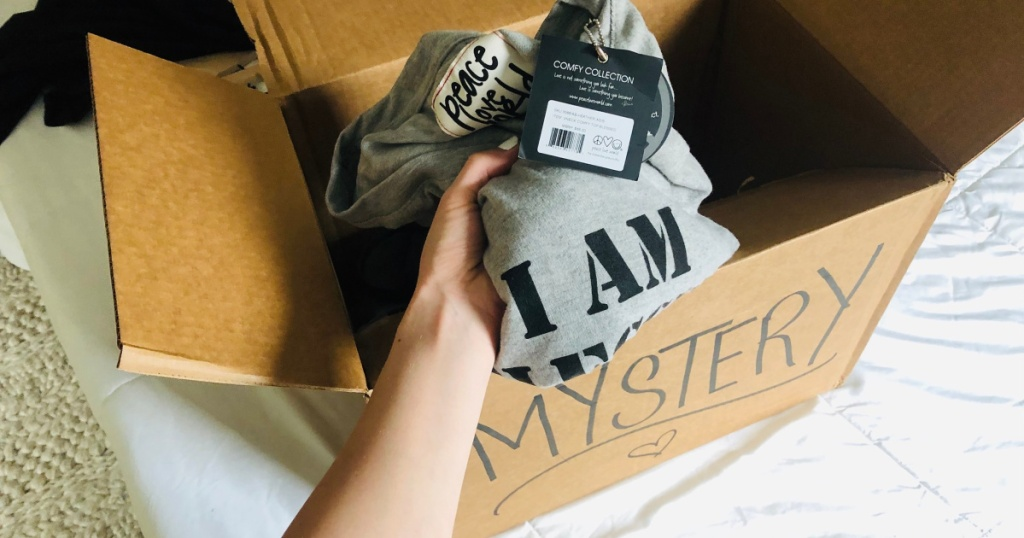 proozy mystery boxes inside of box with hand holding one item