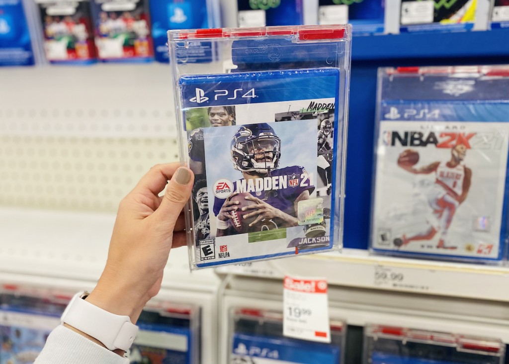 hand holding ps4 madden game on store shelf