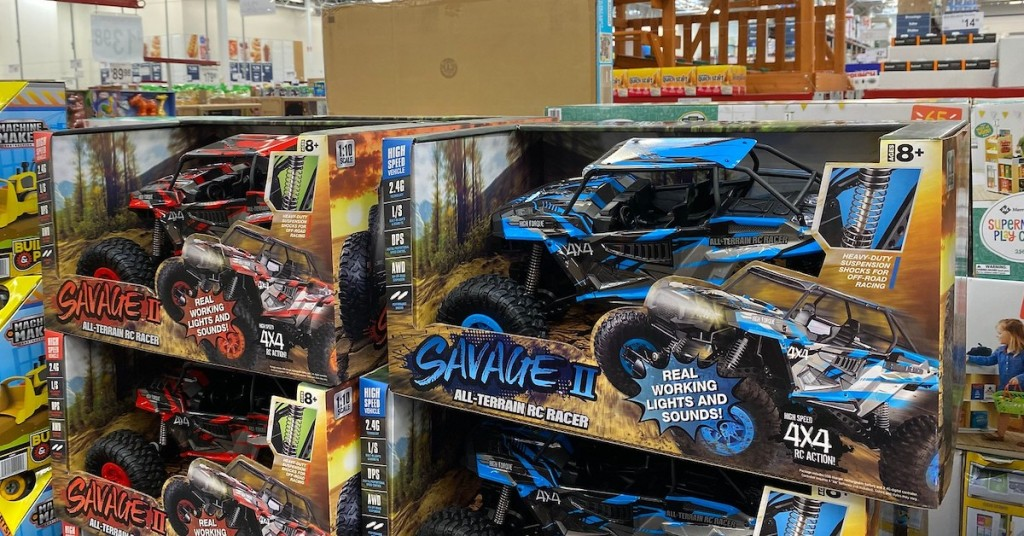 RC Savage remote control cars sitting in boxes in stack on floor