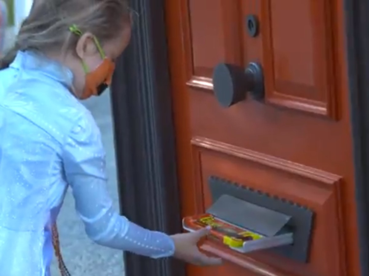 girl getting candy from mail slot on door