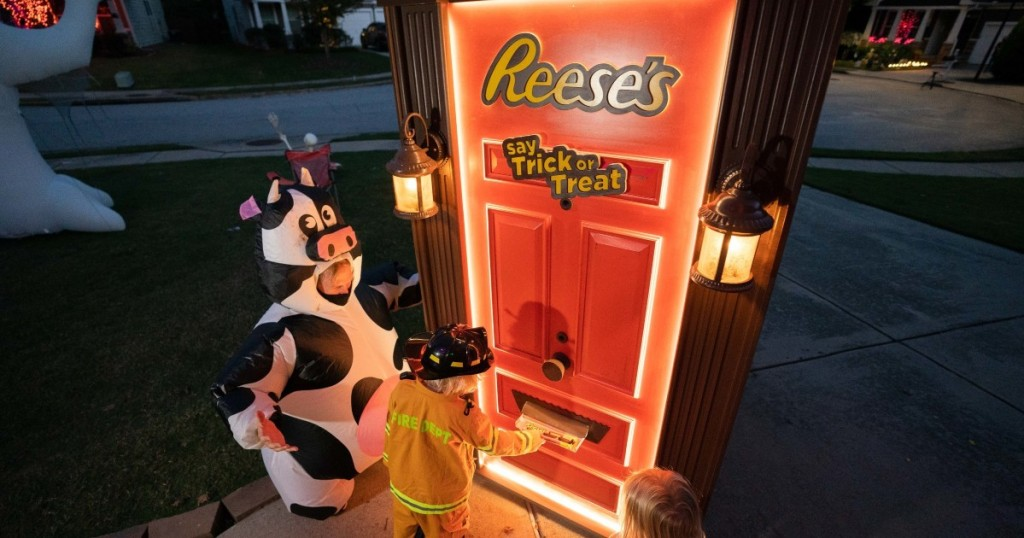 costumed children getting candy from Reese's Trick or Treat door