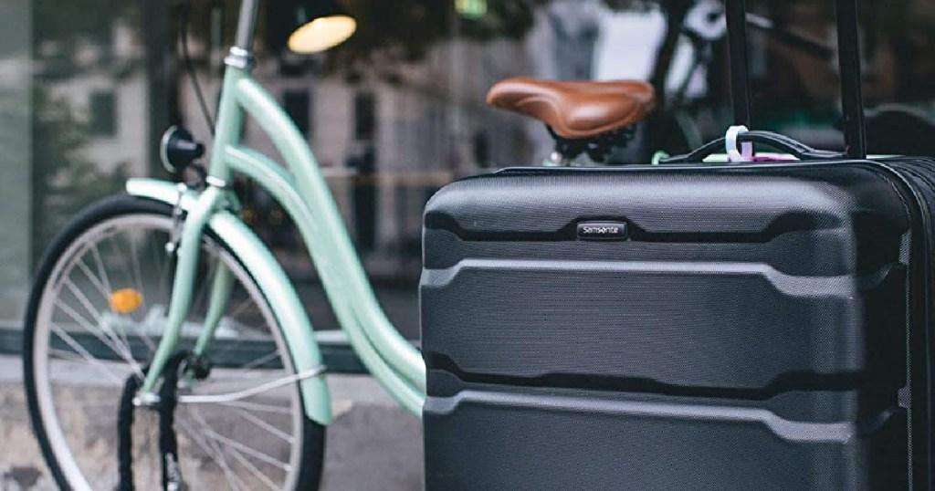 samsonite luggage outside with bike behind it
