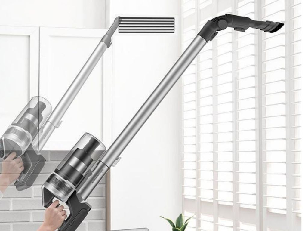 woman cleaning blinds with cordless vacuum