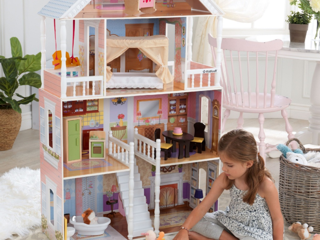 little girl playing with large dollhouse