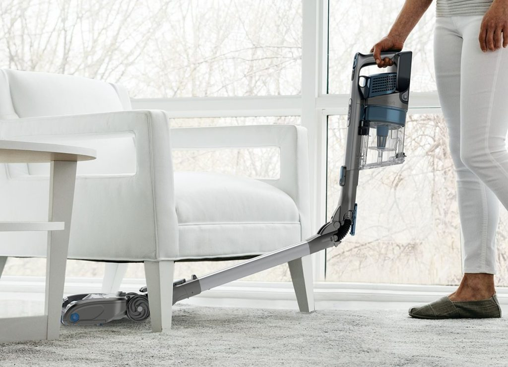 woman vacuuming with shark vacuum under couch