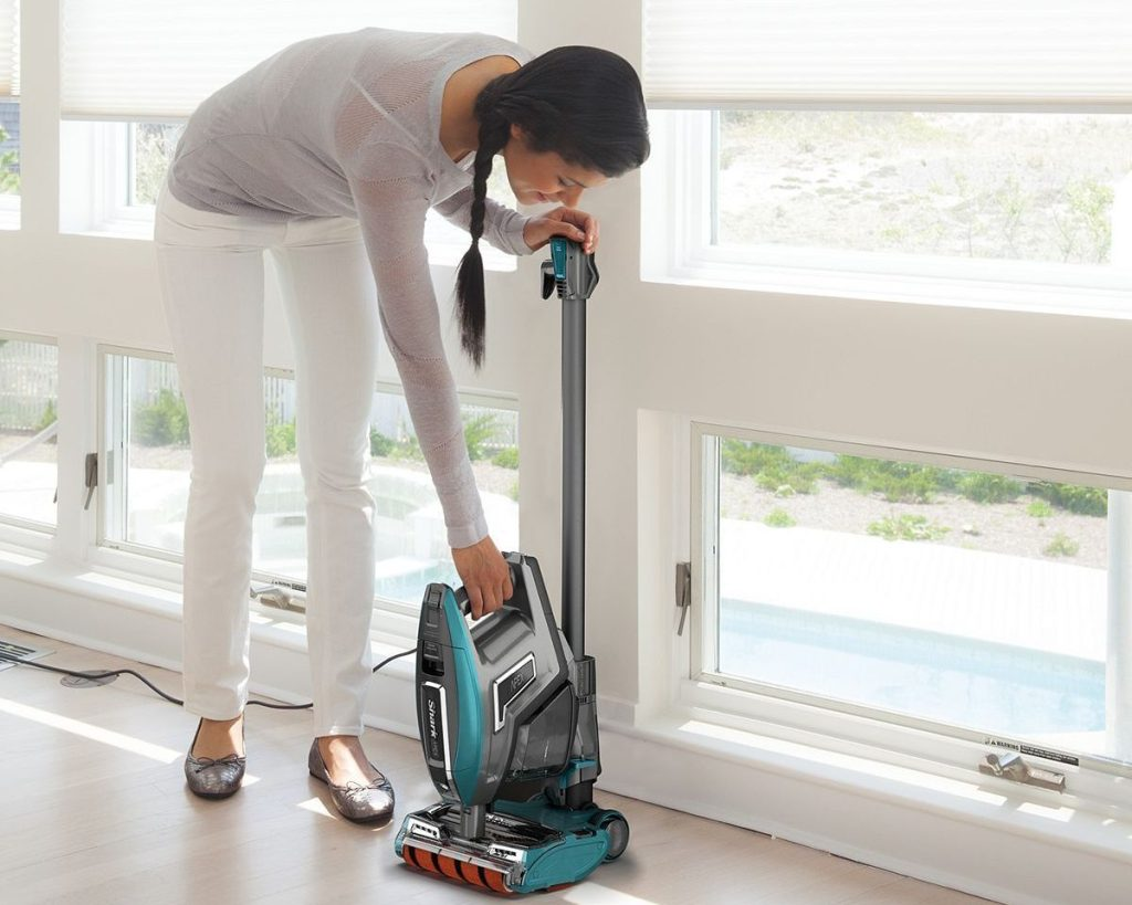 women bending over to clean with vacuum