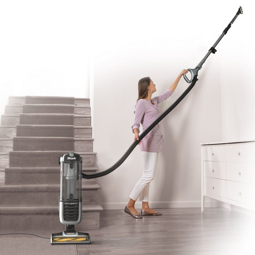 women cleaning ceiling with vacuum