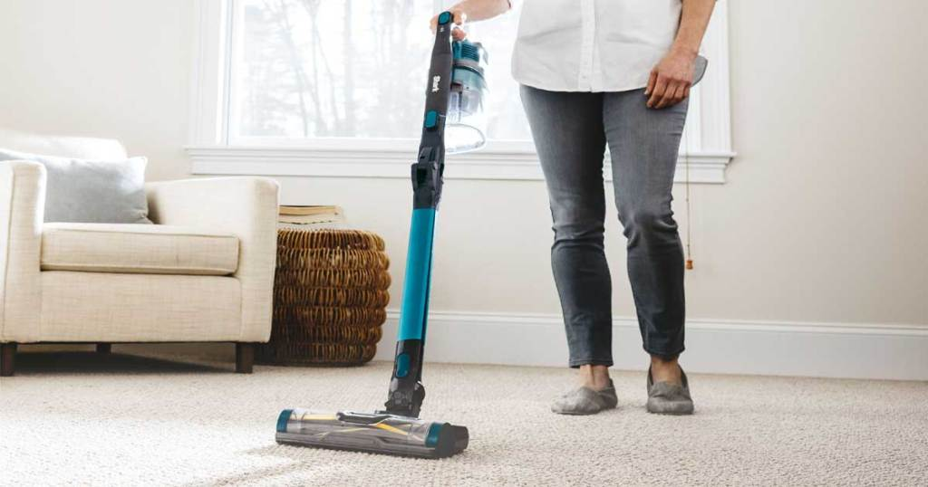 woman pushing a vacuum in a living room