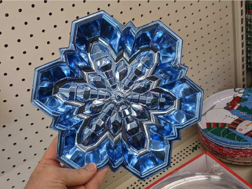 hand holding blue tray shaped like snowflake