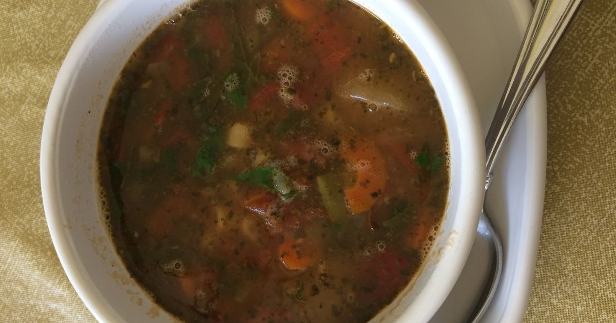 cup of vegetable soup on plate with spoon