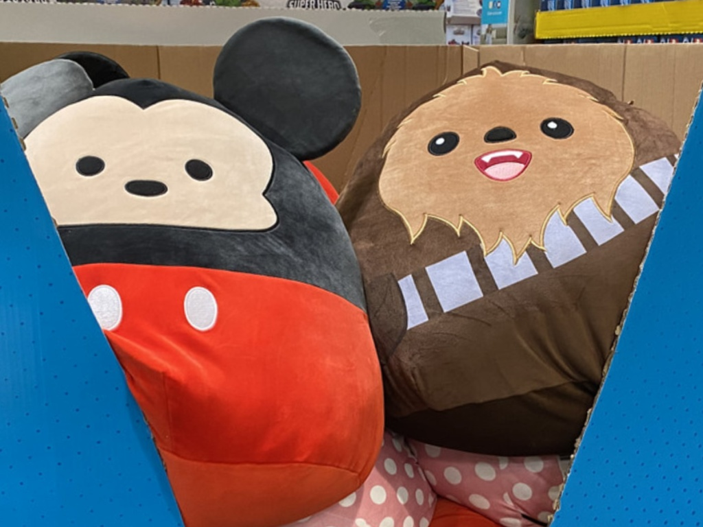 big fat pillows in the shape of Disney Characters in a store bin