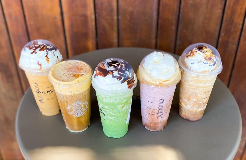 top view of various flavors of starbucks halloween secret menu drinks on table