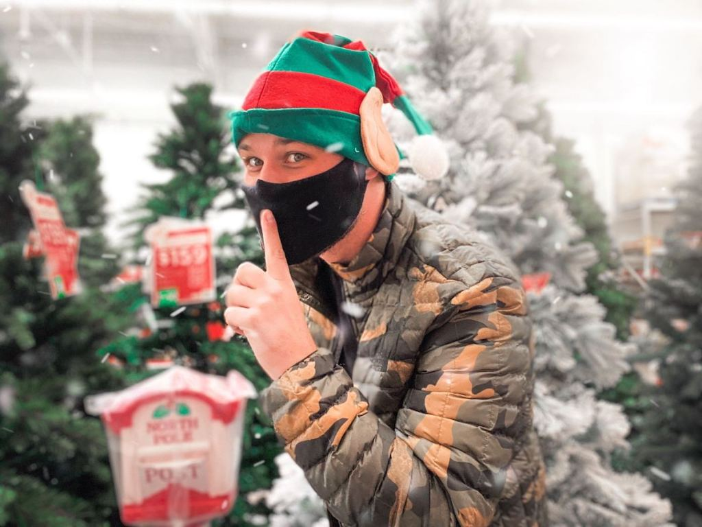 man wearing red and green elf hat and black mask with finger on mouth