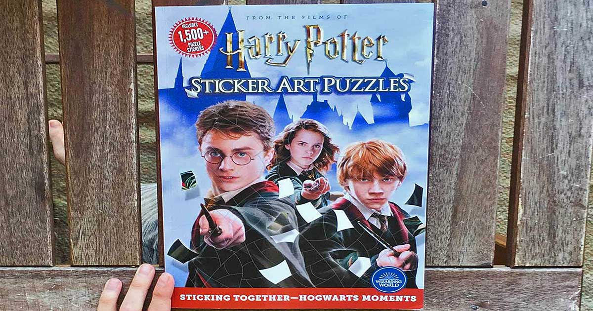 hand holding a harry potter sticker book against a wooden slat fence