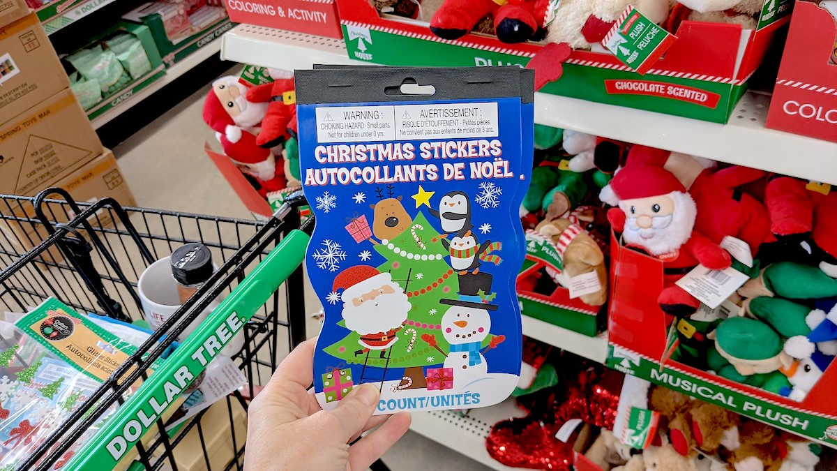 hand holding a pack of stickers books in dollar tree christmas decorations aisle