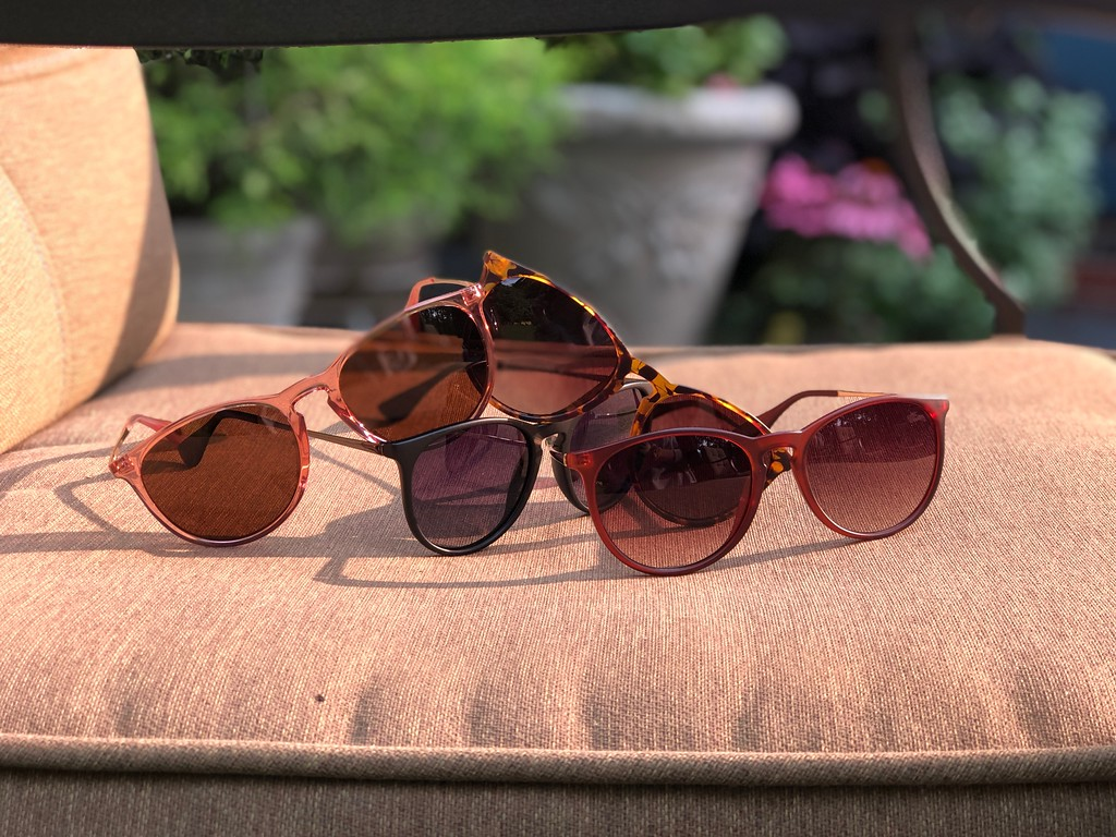 four pairs of sunglasses on patio furniture chair