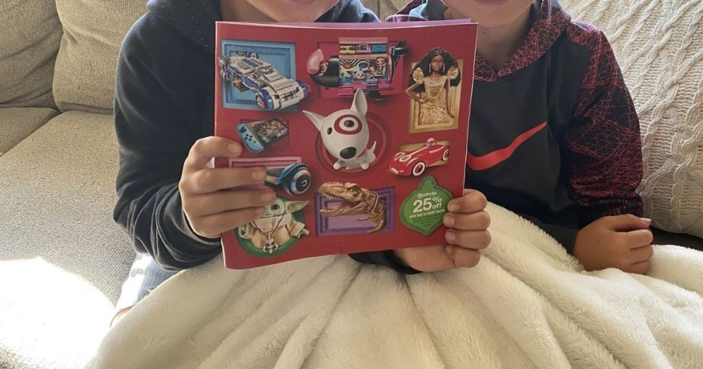 two boys holding up Target toy catalog