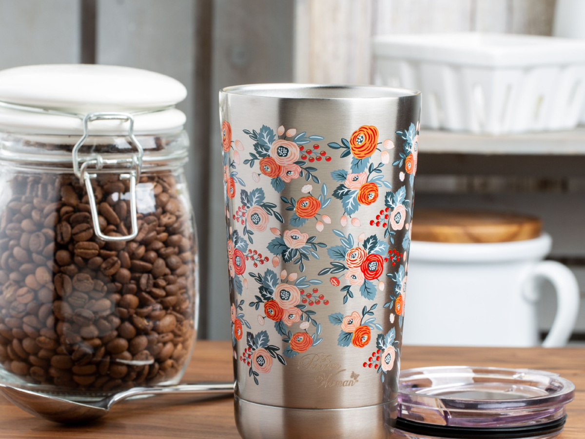 floral print silver tumbler next to coffee beans on counter