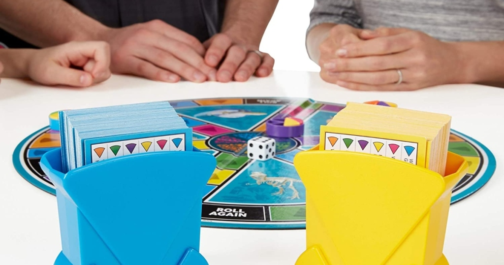 three people around a white table with a game of trivial pursuit. You can only see their hand and the game laid out